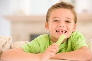 Young boy eating celery